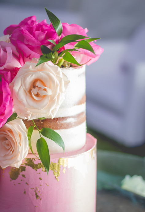 Closeup of Two Tier Buttercream Wedding Cake with Cascading florals and 24K gold leaf