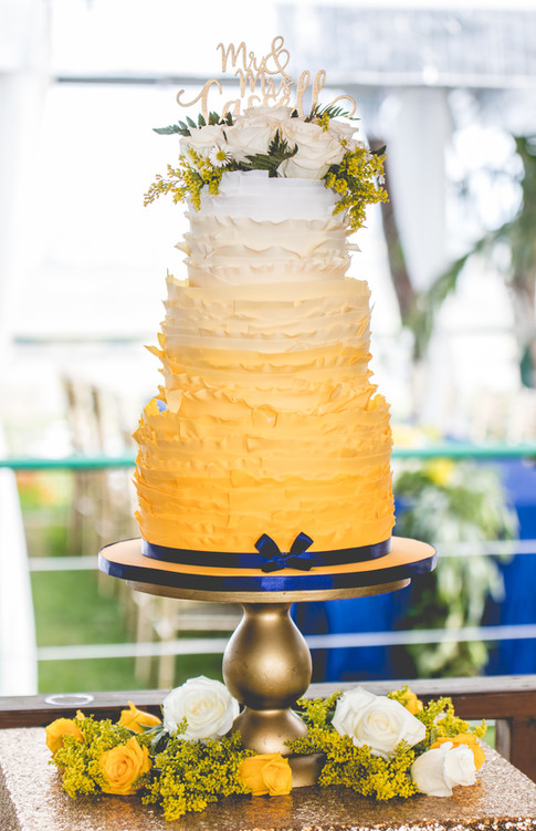 Yellow Ombre Ruffle Wedding Cake topped with Fresh Bouquet of Flowers