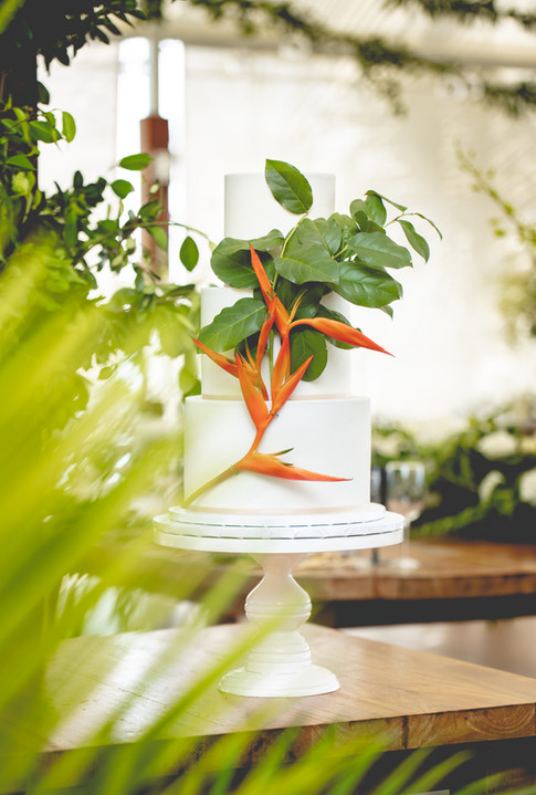 Three Tier Three tier white wedding cake featuring tropical leaves and florals