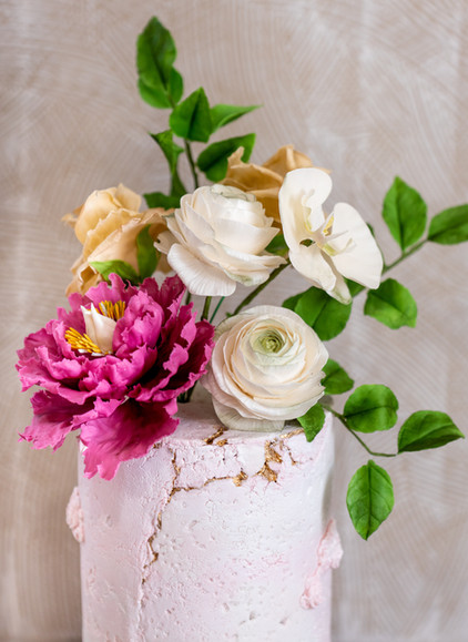 Pink concrete birthday cake featuring sugar flower bouquet