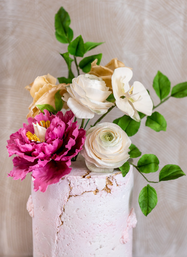 Pink concrete birthday cake featuring sugar flower bouquet