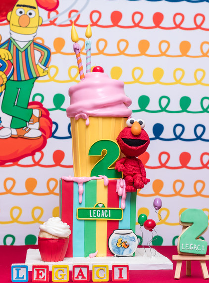Two tier Elmo themed cake featuring giant cupcake