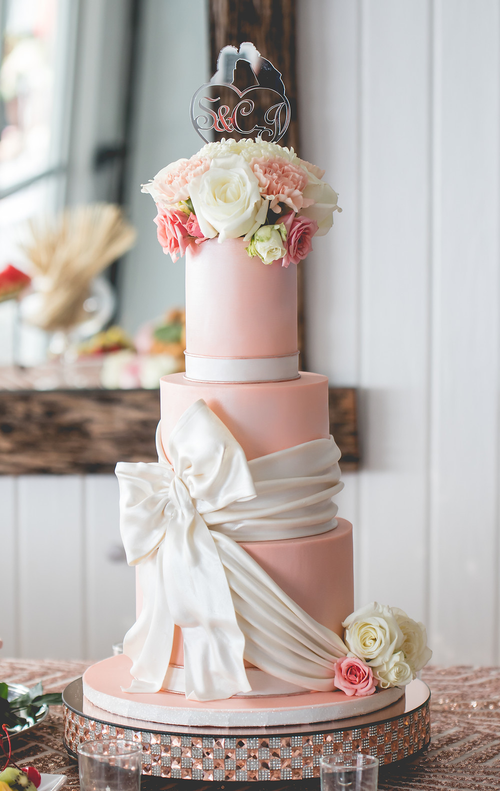 Three tier pearl peach wedding cake with over-sized edible bow and bouquet of fresh flowers