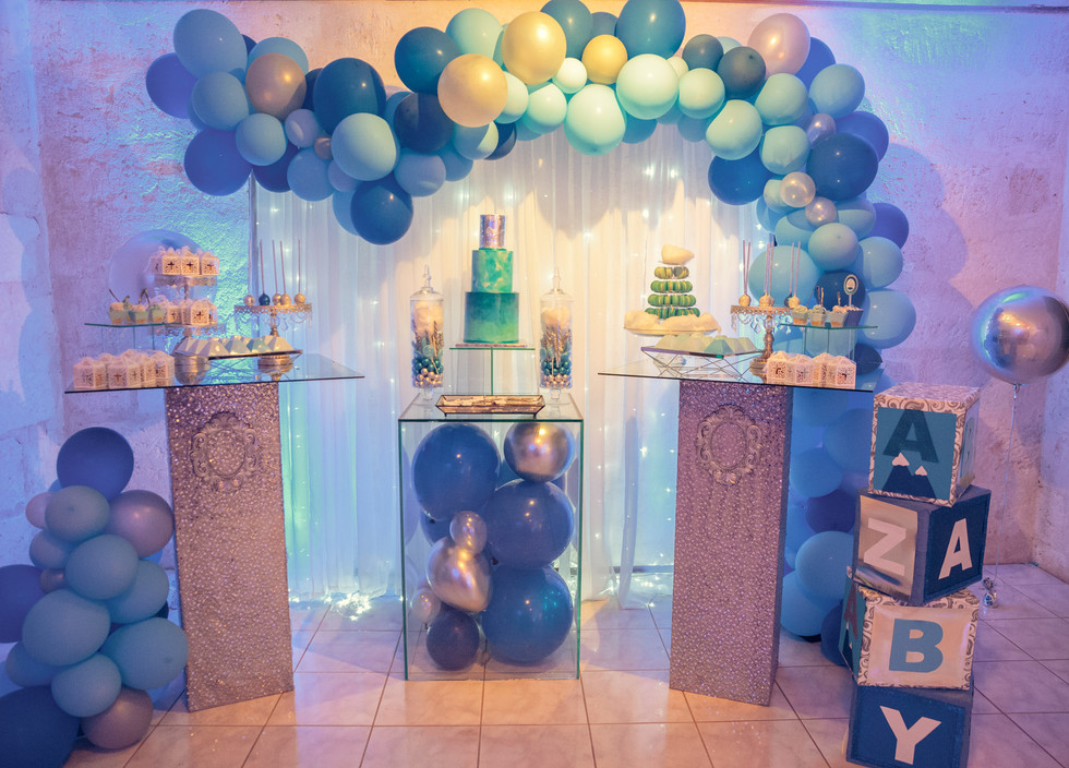 Christening themed Dessert Bar featuring our 3-tier blue ombre and silver cake, sugar cookies, macaron tower, chocolate pyramids, cupcakes and cake pops.