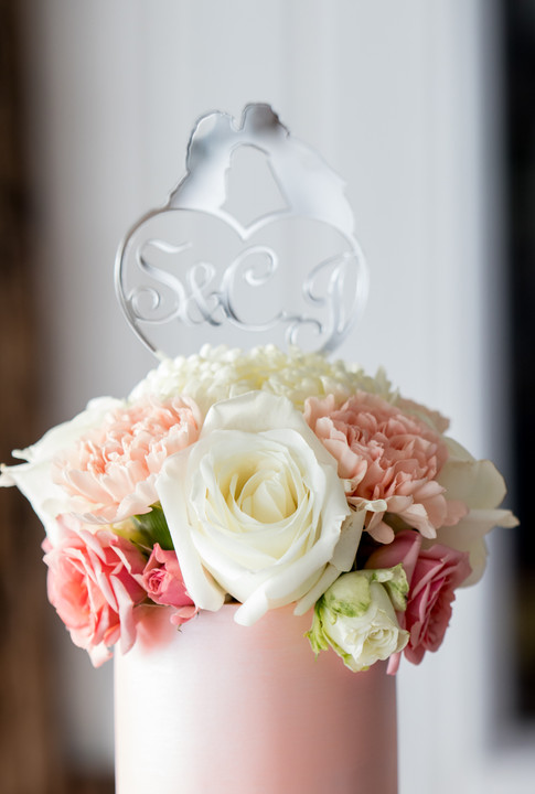 Closeup of Peach Wedding Cake and Bouquet of Fresh Flowers