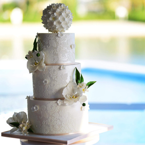 All white three tier wedding cake featuring handmade orchids and hydrangea pomander