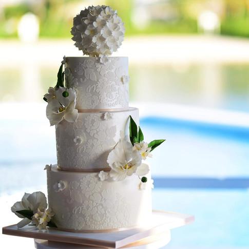 All white three tier wedding cake featuring handmade orchids and hydrangea pomander