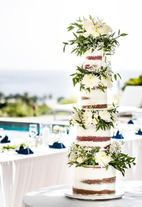 Four tier semi-naked wedding cake featuring fresh white flowers