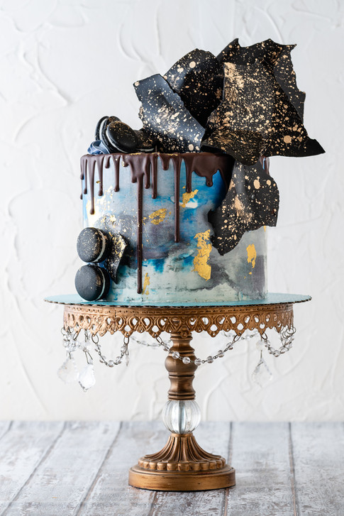'Galactic': Watercolor Buttercream Drip Cake finished in black and gold chocolate chards and black macarons