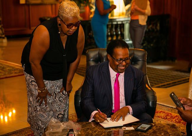 Debra Harvill looks on as Edgar vann signs book