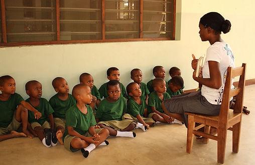 Miriam, ein Volunteers aus Simbabwe gibt Untericht auf Montessori basis