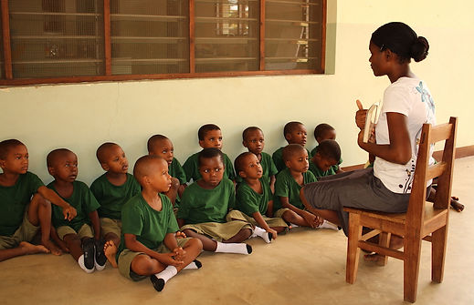 Montessori Volunteer from Simbabwe is giving a lesson to medium class