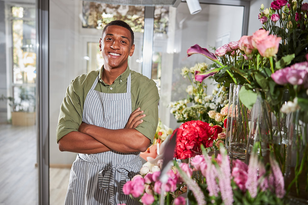 Optimistic florist standing near a big flower display with his arms crossed below his ches