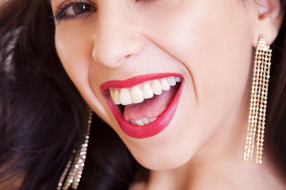 Woman in long gold shoulder duster earrings