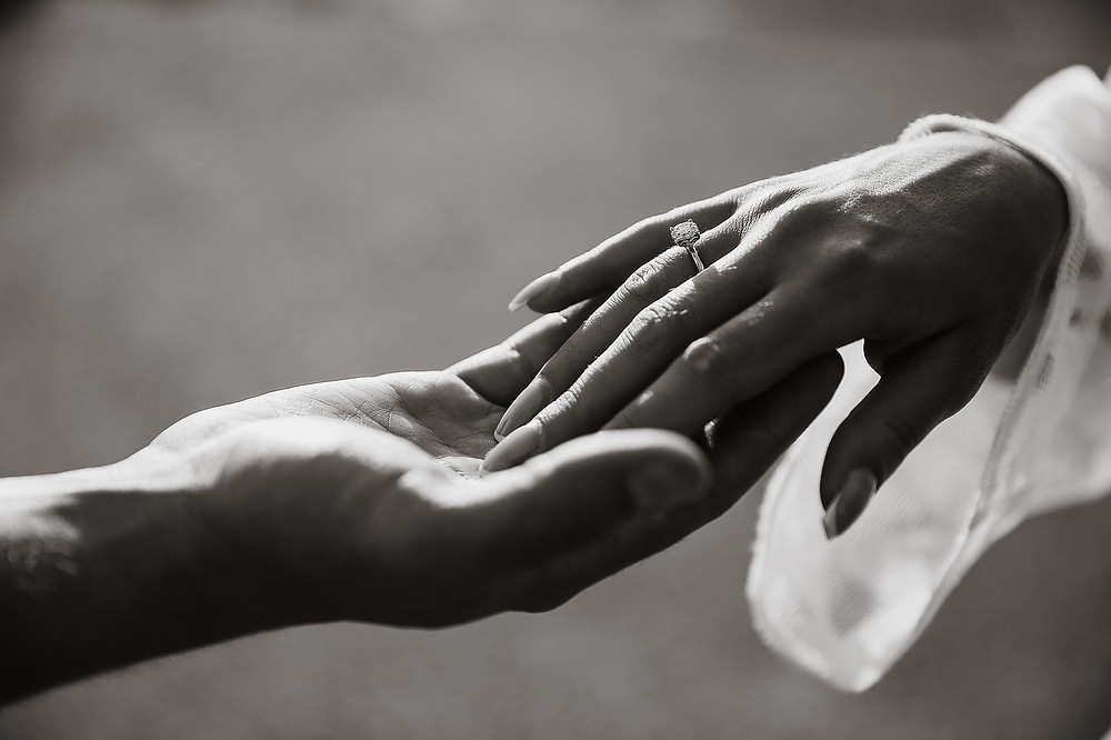 Black and white photo of an engagement ring being worn on the right hand