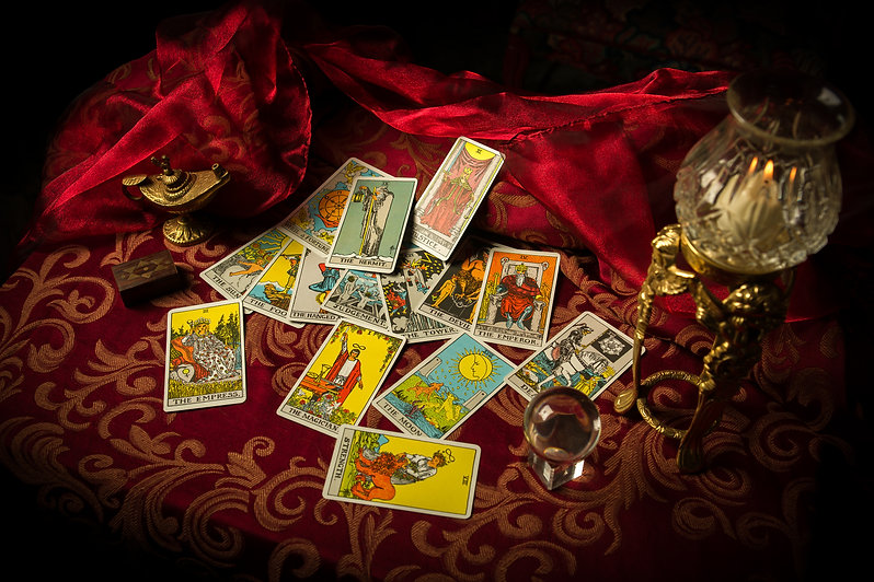 A pile of tarot cards lie scattered and