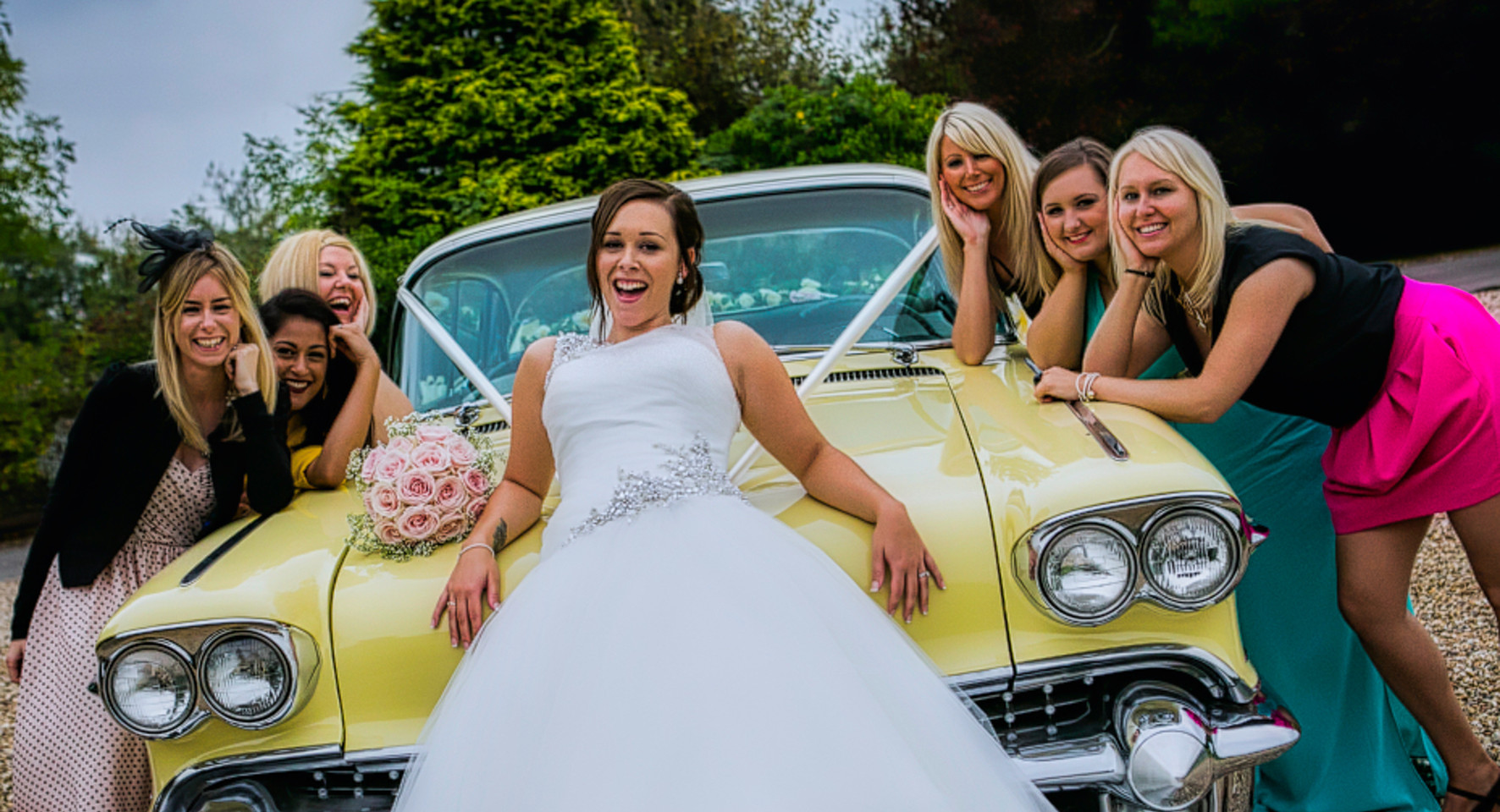 bride and bridesmailds on yellow american car