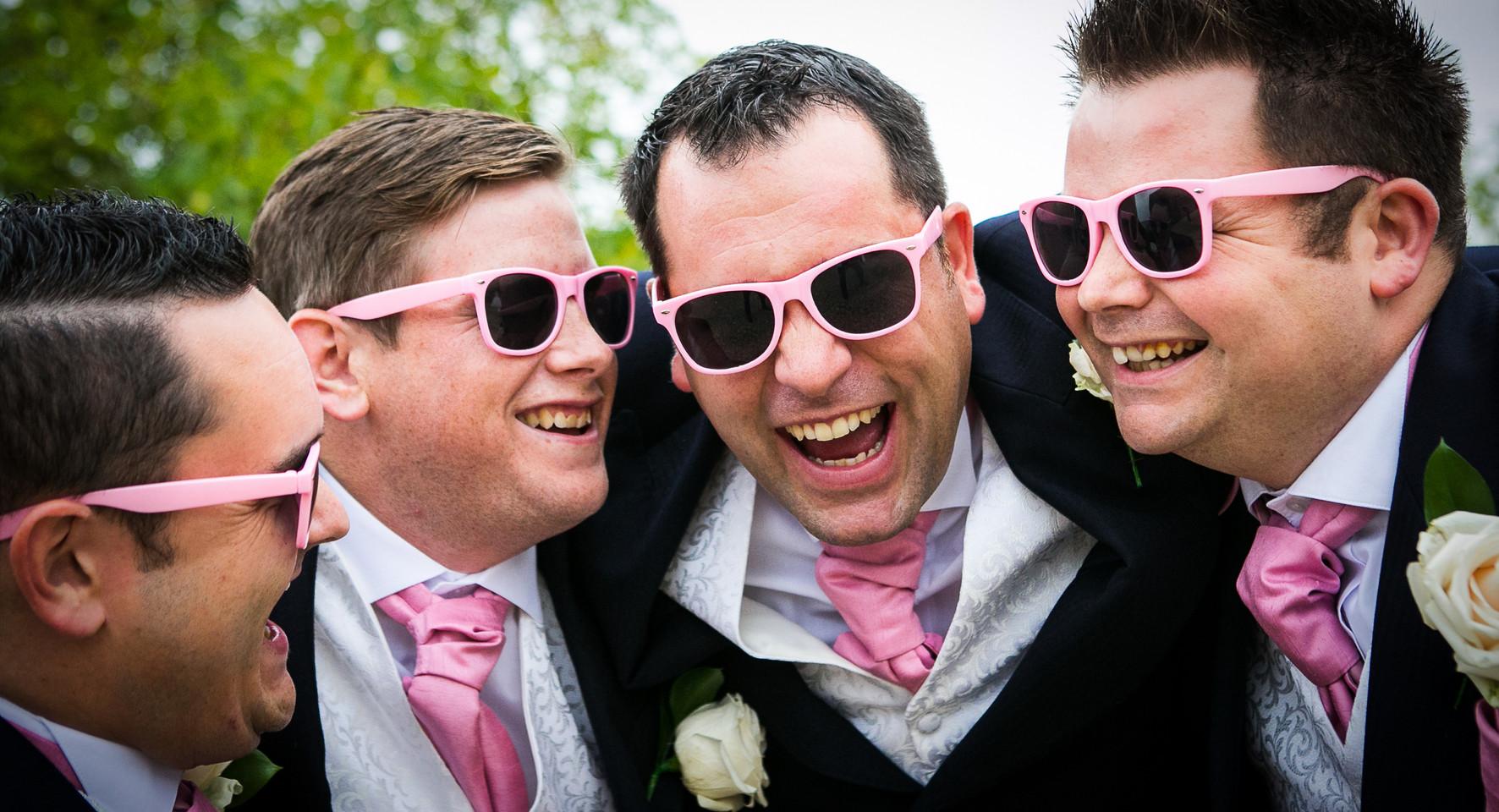 groomsmen with pink flowers