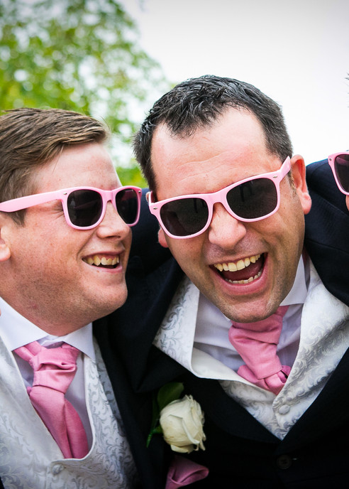 groomsmen with pink flowers