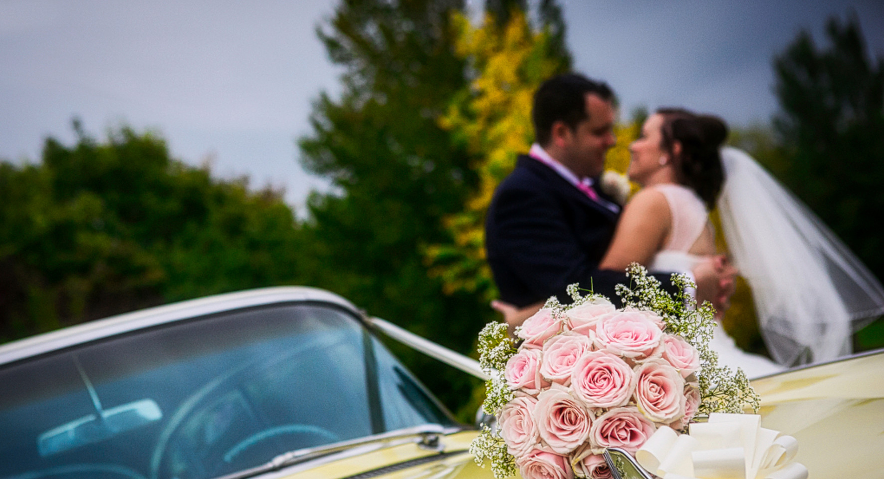 beide and groom distance kiss, car, flowers