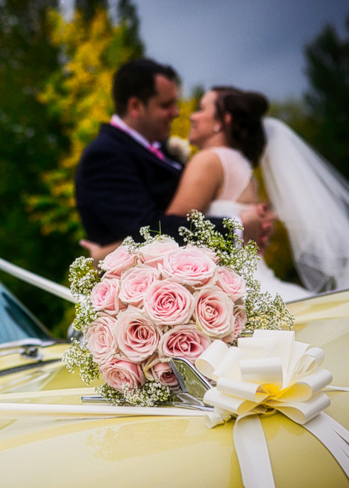 beide and groom distance kiss, car, flowers