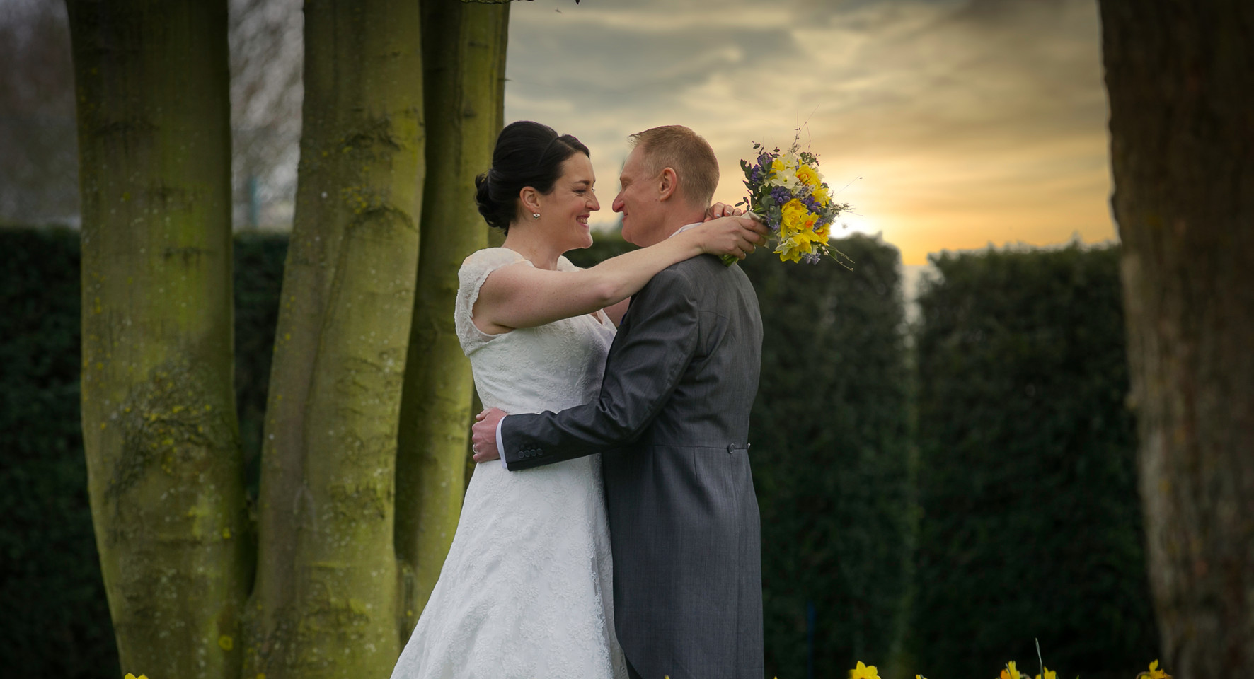 bride and groom sunset kiss daffodils