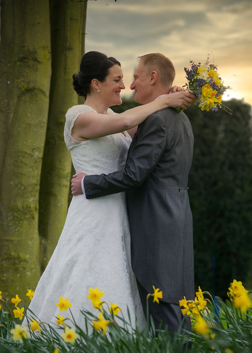 bride and groom sunset kiss daffodils