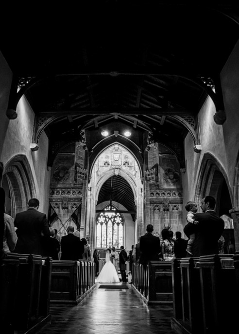 bride and grrom at altar distance black and white