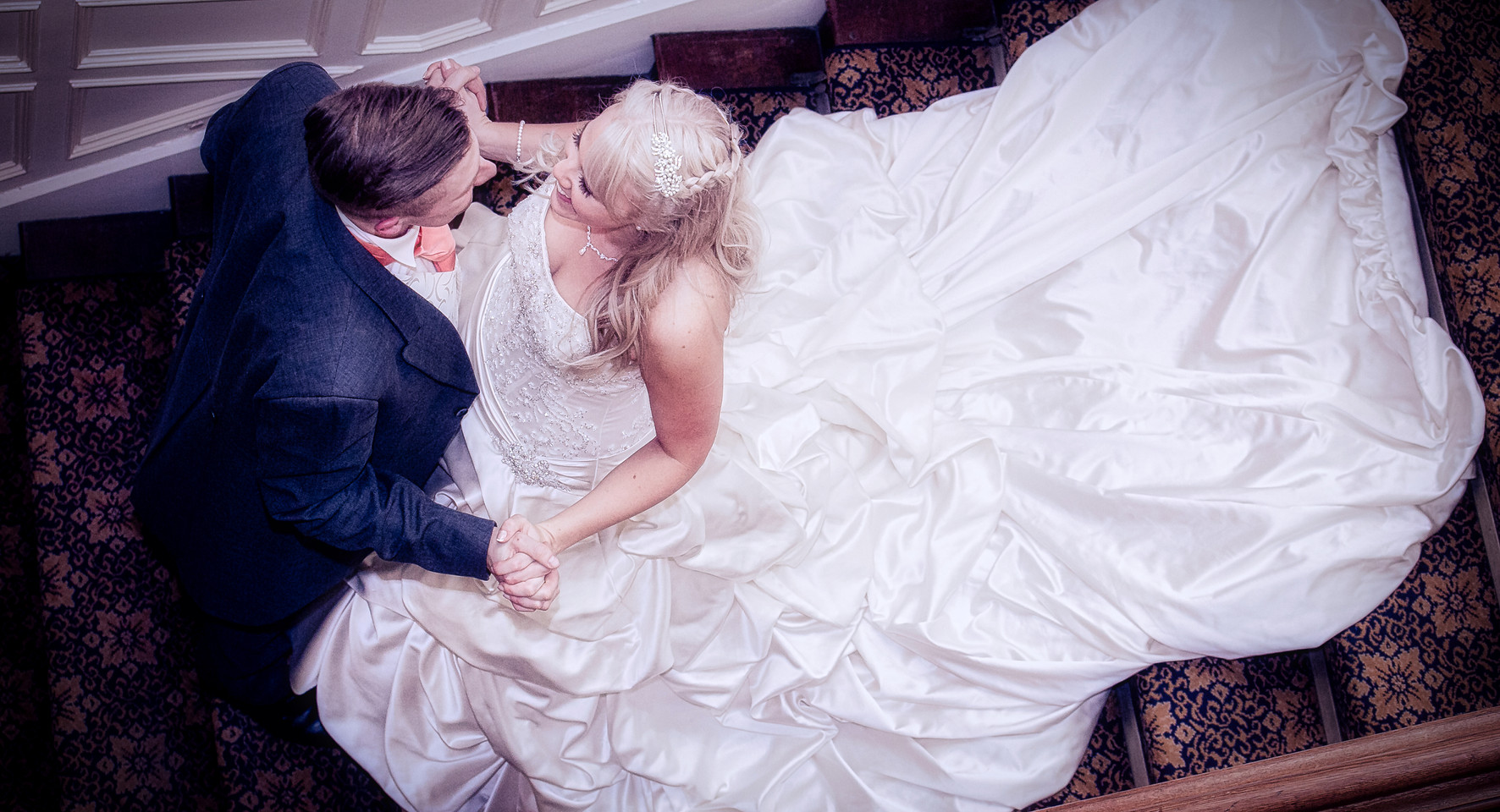 bride and groom on stairs look down dress