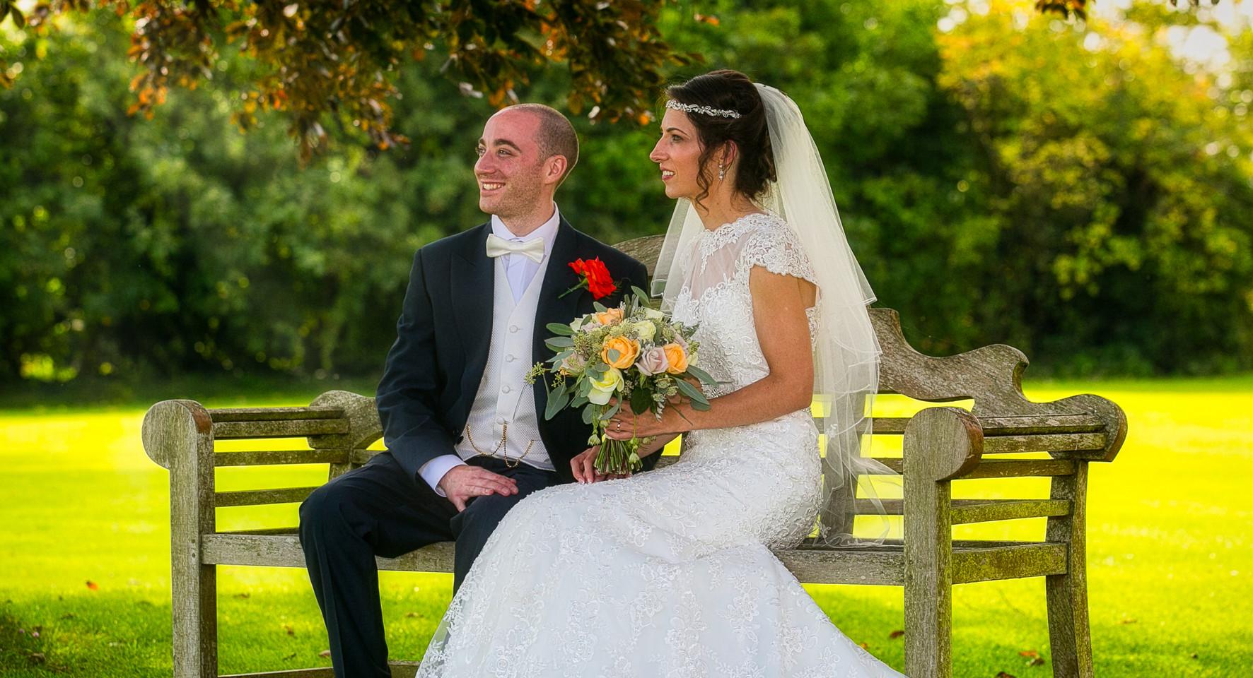 beride and groom sit in garden sunshine