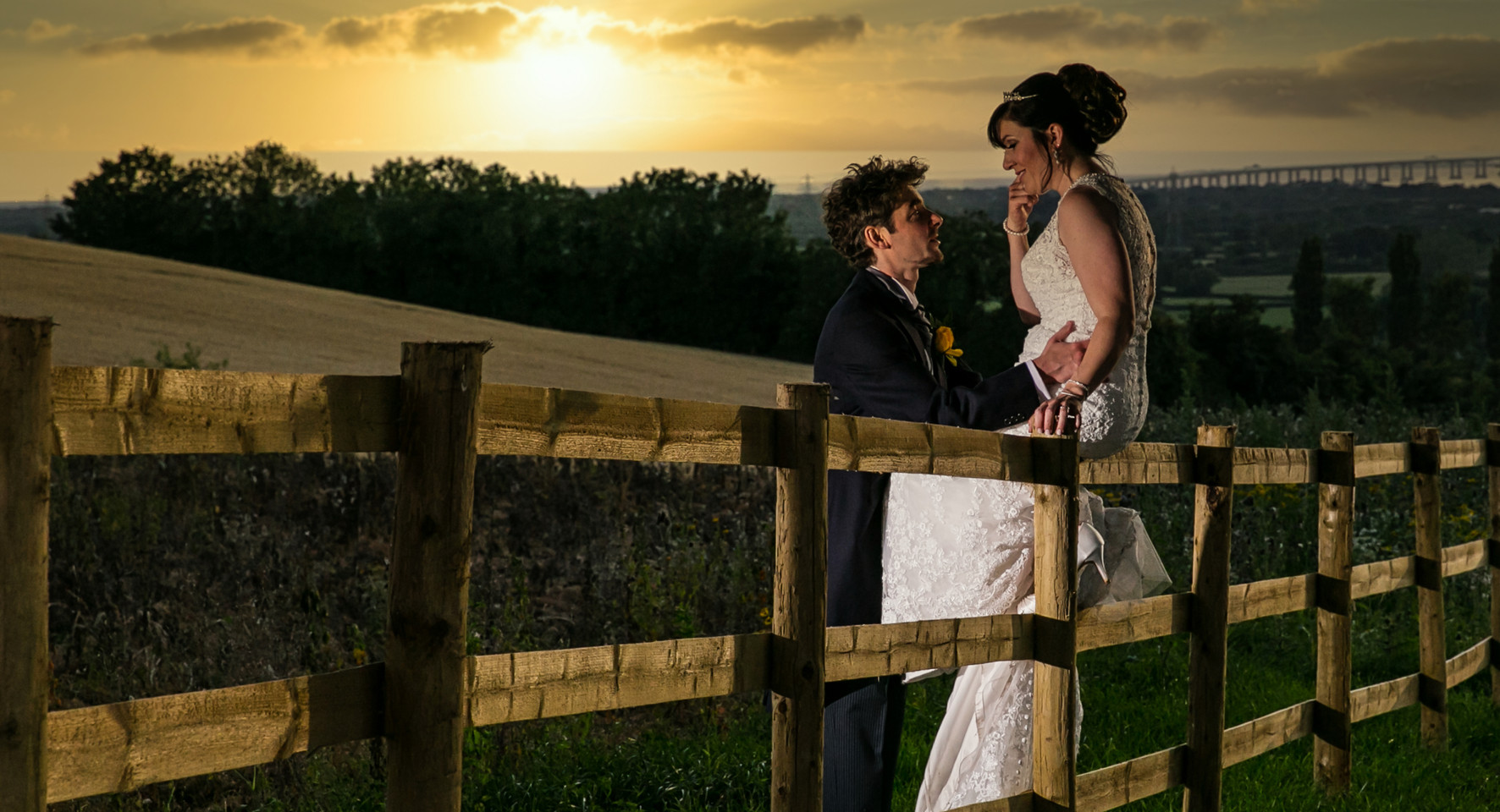 bride and groom sunset fence