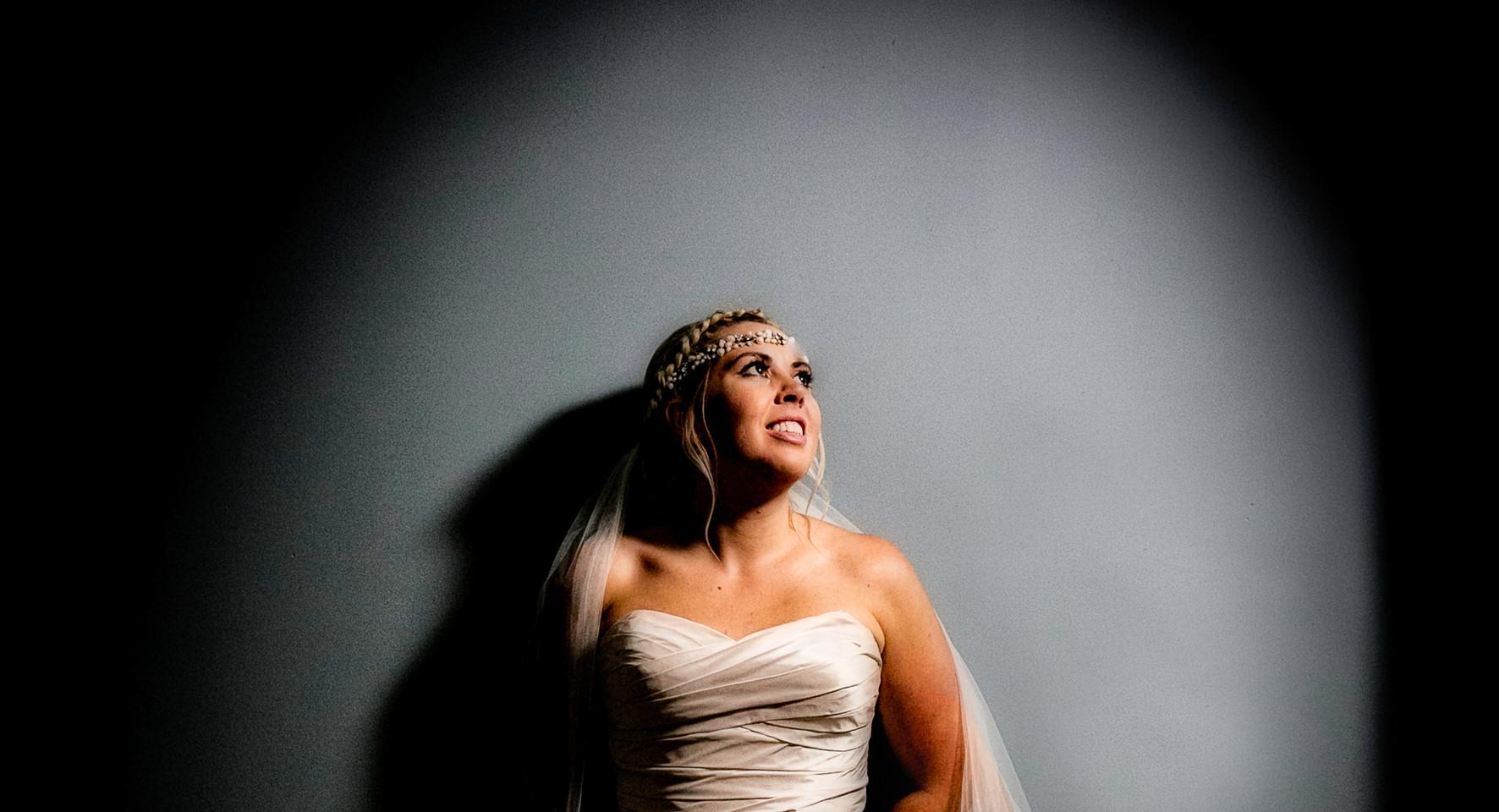 brautiful bride resting against wall spotlit