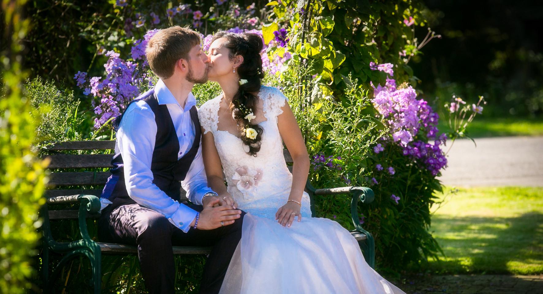 bride and groom it in garden kiss