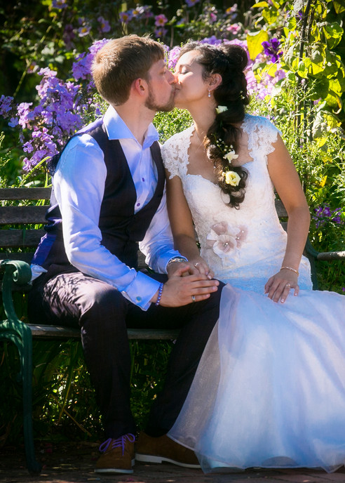 bride and groom it in garden kiss