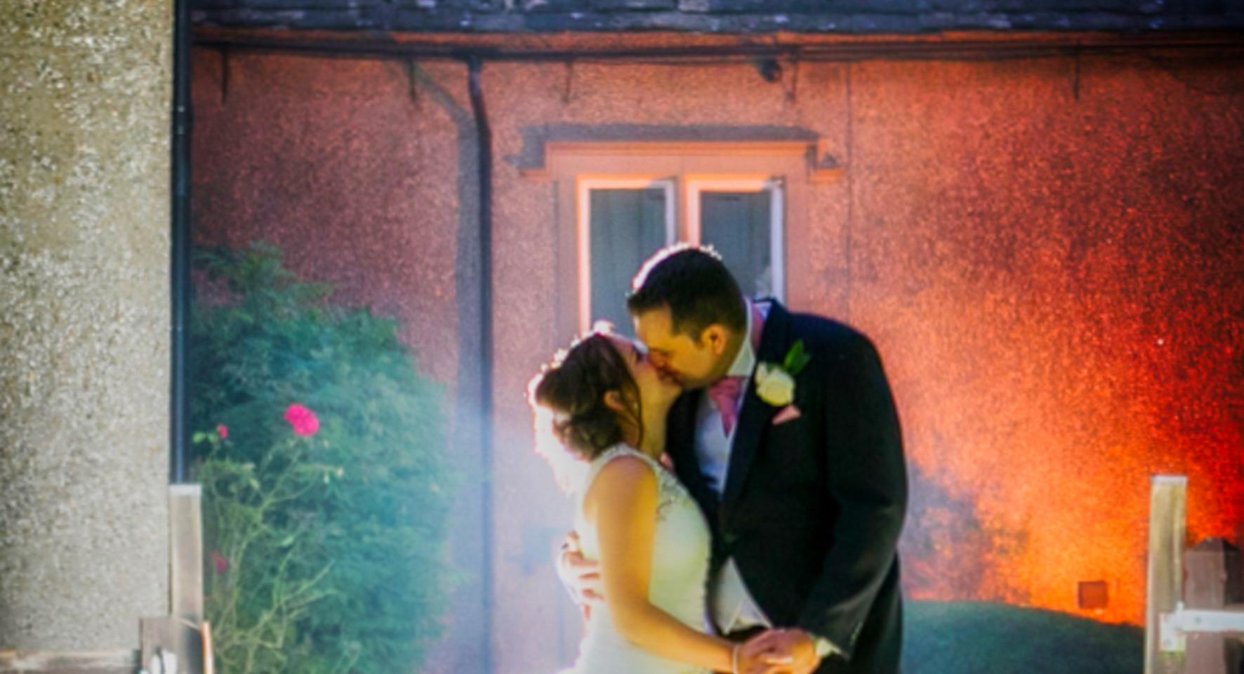 bride and groom kiss backlit flash