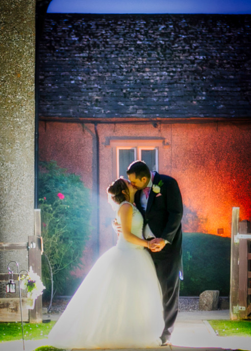 bride and groom kiss backlit flash