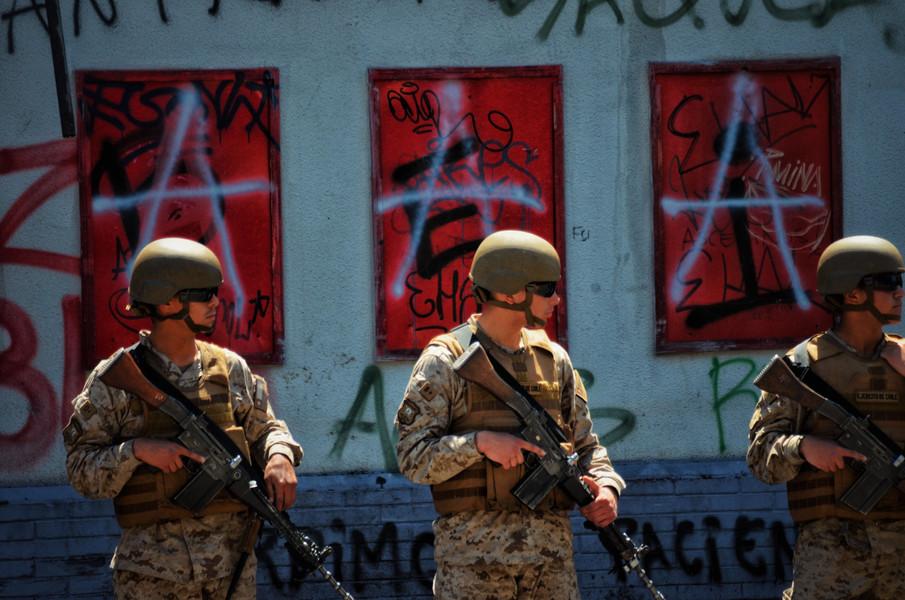 Valparaiso, au lendemain du début des hostilités au niveau national. Les militaires montent la garde devant un supermarché chilien qui a flambé pendant la nuit. Les rues sentent le brûlé, plusieurs magasins ont été pillés et les murs de la ville sont déjà couverts de revendications.