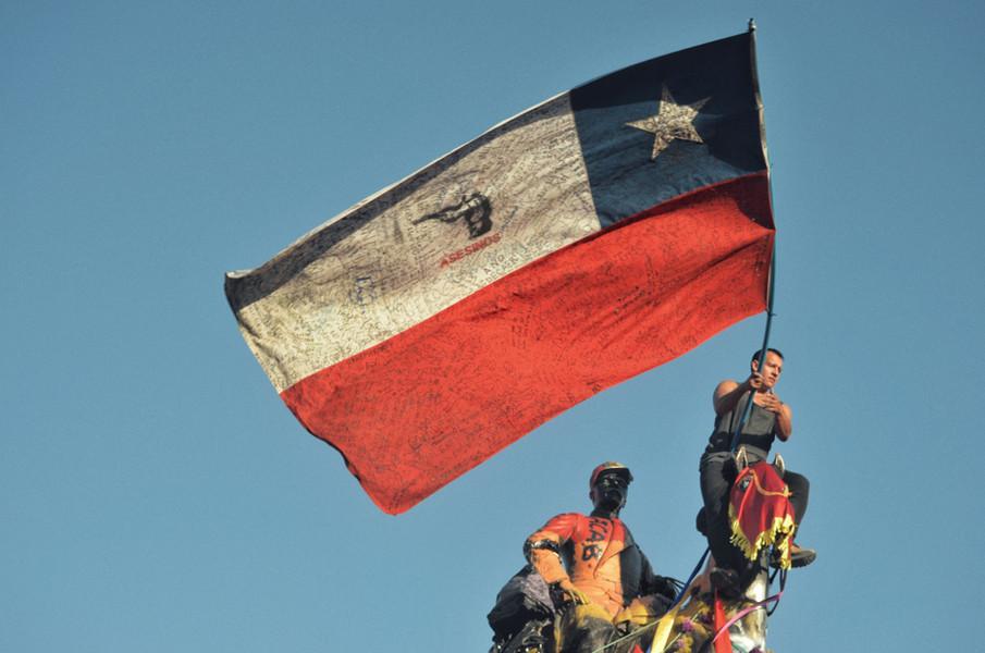 Pour brandir des drapeaux détournés ou lancer des chants et clapping, certains s'aventurent à chevaucher la statue  du général Baquedano repeinte en rouge pour symboliser la répression dont le peuple chilien est victime.