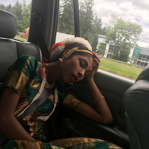 Dancing and getting ready in full costume is tiring. Sometimes, a dancer has to catch a snooze on drives :)