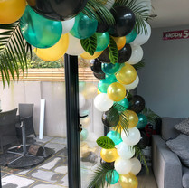 Balloon arch with tropical foliage