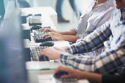 Os estudantes de digitação em seus compu