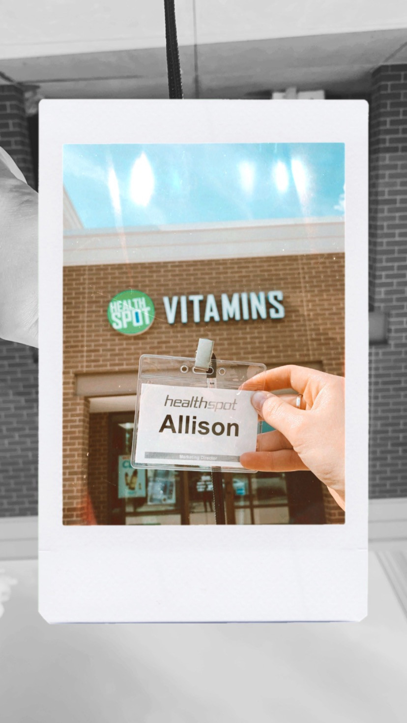 """My hand holding my badge that says """"Health Spot/Allison/Marketing Coordinator"""" up against the Health Spot store sign."""