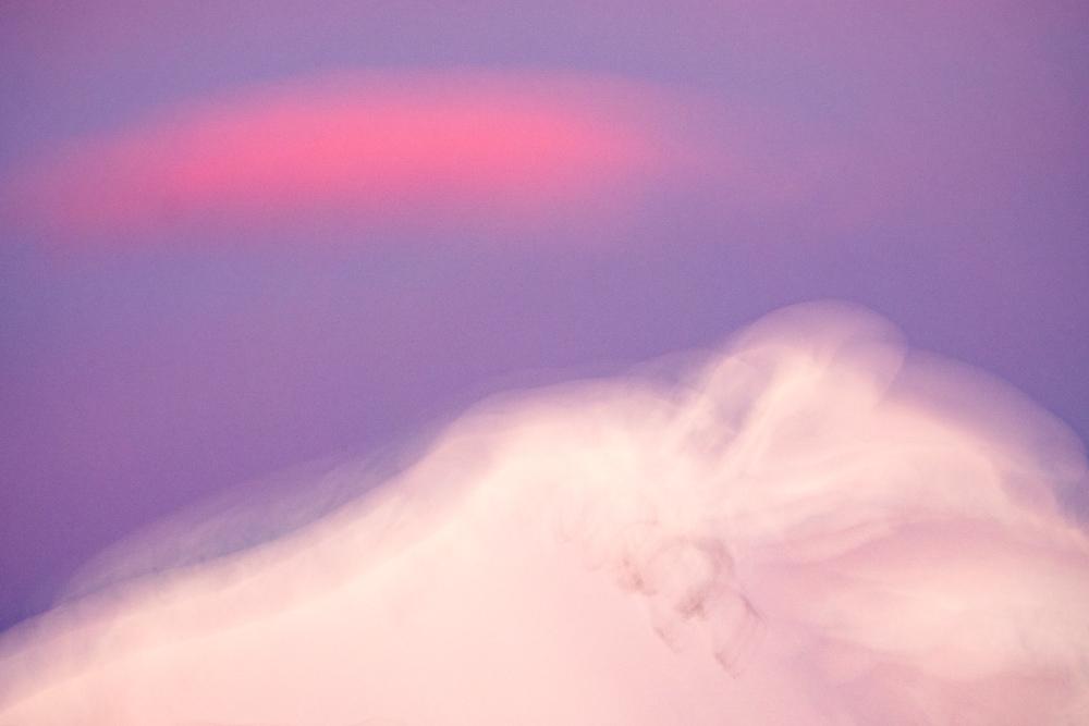 Niemimaan vuoret ulottuvat pilviin saakka, vaaleanpunaisiin pilviin. Yli 3000 metriä korkeat seinämät lähtevät kohoamaan suoraan merenpinnasta.