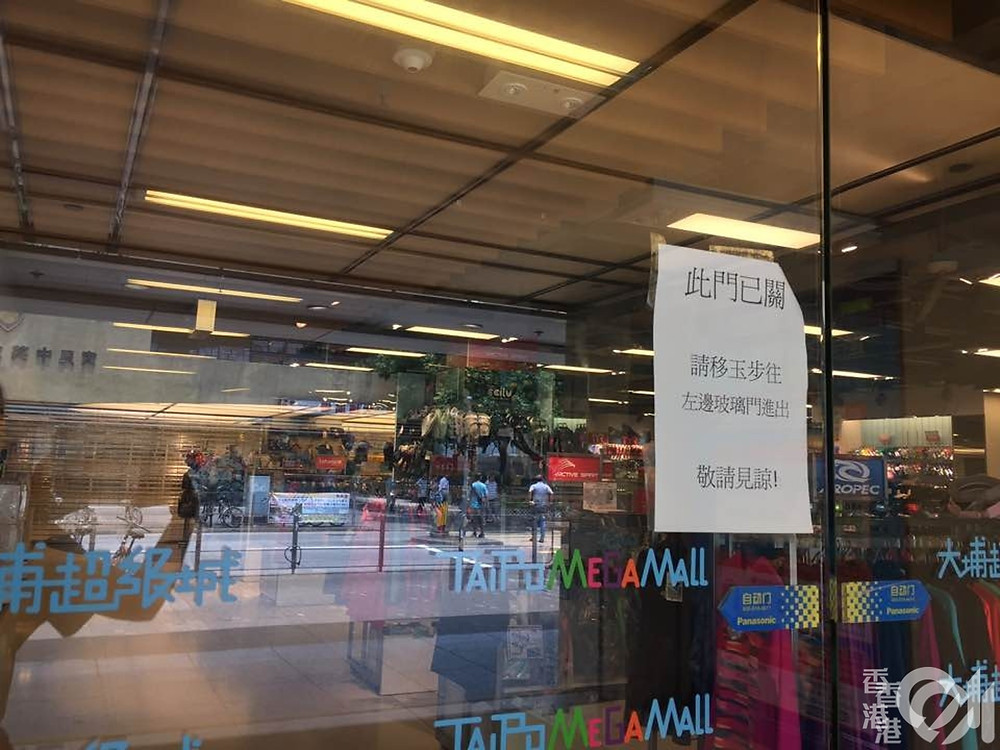 PHOTO FILE: They blocked police from entering in it. The automated door is blocked by a staff of Sun Hung Kai Properties Ltd. at Tai Po Mega Mall on August 14, 2019. © HK01 / Li Zhizhi
