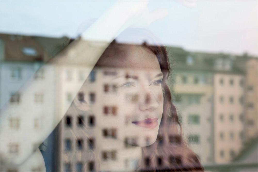 FILE PHOTO: A Woman Seeing Real Estates Through Window. ©WiX