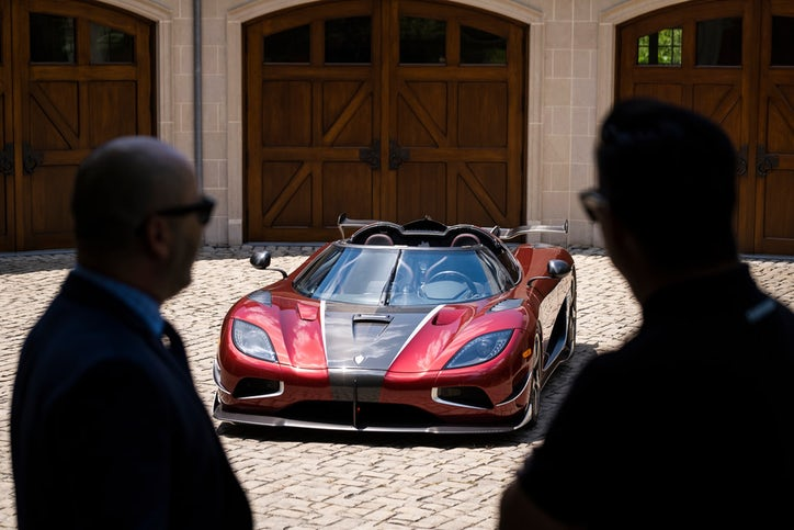 Visitors are silhouetted as they see the Koenigsegg Agera RS on display in the driveway of Ted Skokos' carriage house. (Smiley N. Pool/Staff Photographer)