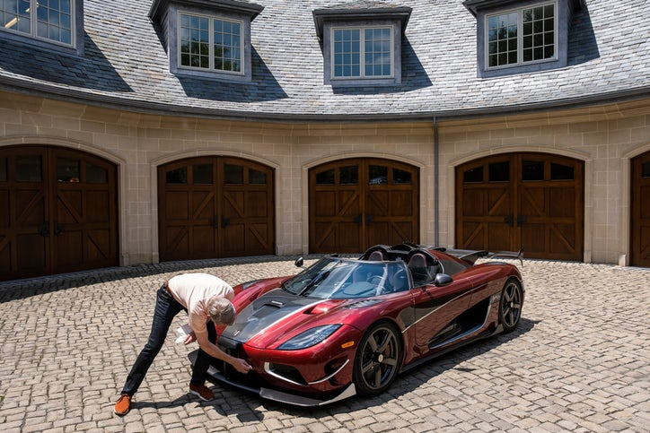 Ted Skokos wipes down a Koenigsegg Agera RS on display in the driveway of his carriage house. (Smiley N. Pool/Staff Photographer)