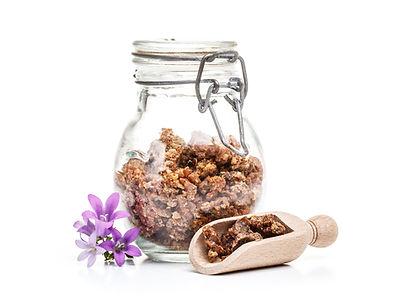 Propolis granule in glass jar and in wooden spoon.jpg