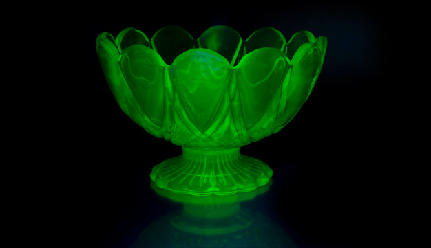 Bowl made from glass with uranium added to the mix before melting. This process makes it mildly radioactive, the presence of uranium causing it to glow under UV or black light. Art Deco in style, glassware of this type was also known as Vaseline glass due to its colour.  20th century. (2021)