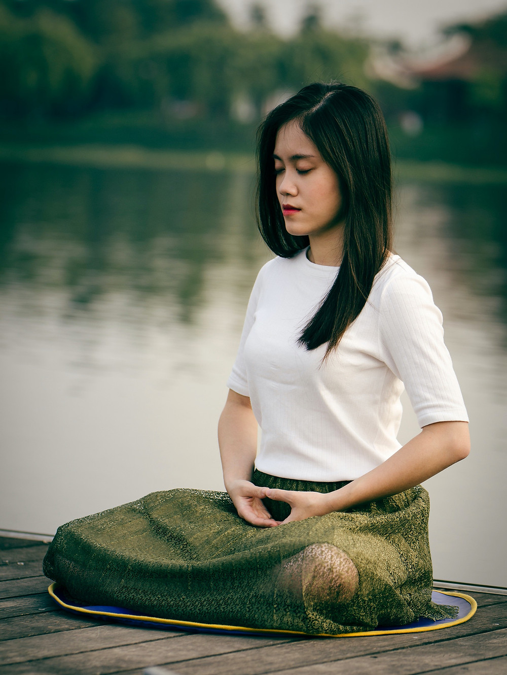 Girl meditating by the water